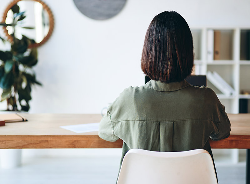 How to adjust office chair: woman sitting at desk
