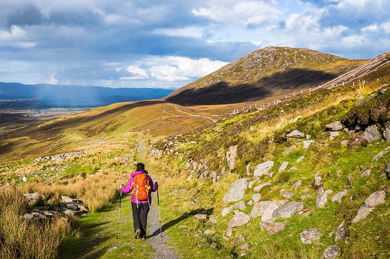 Woman Nordic walking in rolling countryside