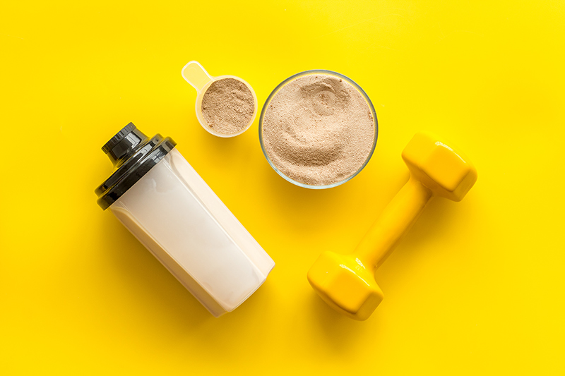 Post-workout protein shake, protein powder, and dumbbell